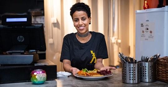 Eritreisk kvinne serverer en tallerken mat.
