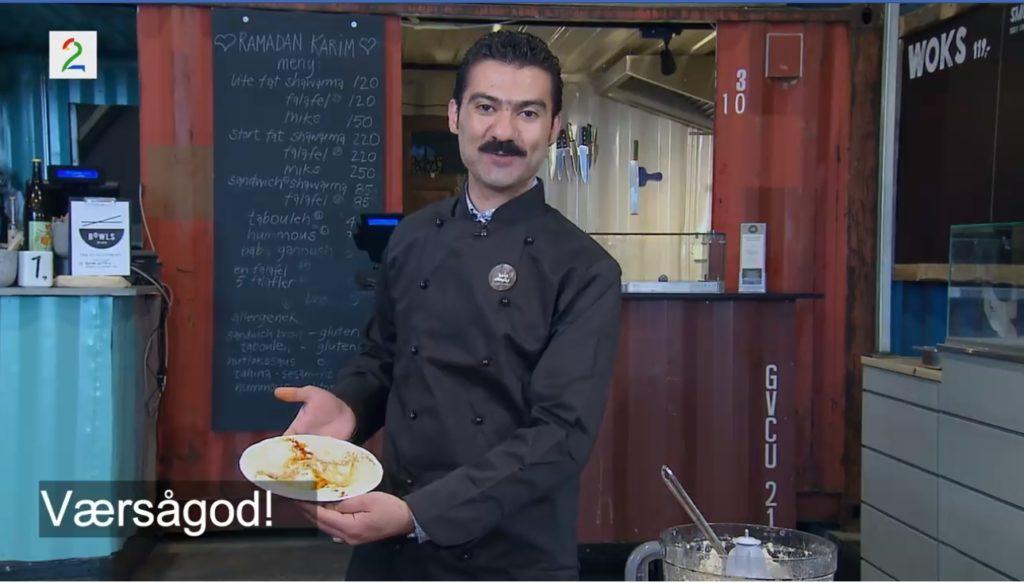 Kokken Mohamad Hadri holder frem en tallerken med hummus.